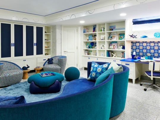 This undated photo provided by Jenny Kirschner shows a basement designed by the New York-based interior designer. Closed storage and ample shelving help keep this basement playroom feeling organized, while layered rugs and soft upholstery add plenty of warmth in this basement.