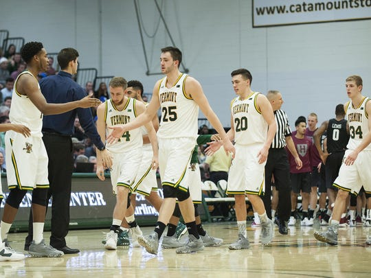 Vermont heads to the bench for a timeout during the men's basketball game between the Harvard Crimson and the Vermont Catamounts at Patrick Gym on Monday night.