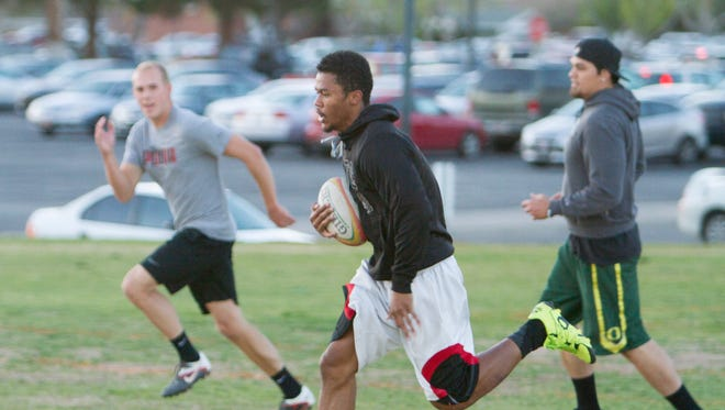 Members of the Dixie State rugby team take part in practice Wednesday night at Encampment Mall.