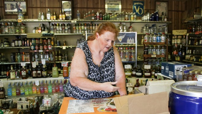 Deborah Howard stocks the shelves of University Package Store. She, like other liquor store owners and managers in Clarksville, are concerned about city council's recent decision to remove the cap on liquor stores. The city allow more liquor licenses starting in 2018.