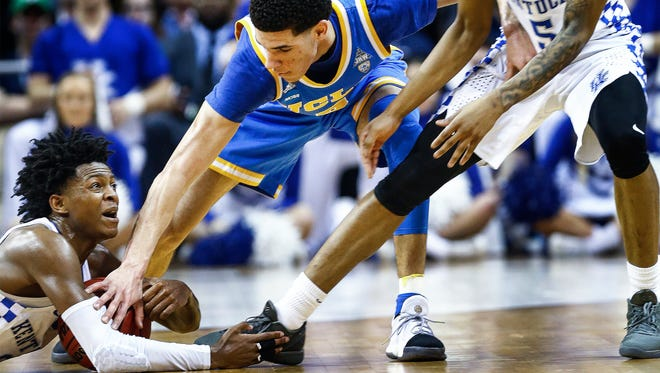 University of Kentucky guard De'Aaron Fox (left) grabs a loose ball in front of UCLA defender Lonzo Ball (right) in their NCAA tournament Sweet Sixteen matchup at the FedExForum.