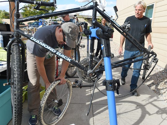 Daniel McFee and Matthew Carlson repair a bike at the Murphy Center on Friday, September 30, 2016. Volunteers help the homeless overcome transportation issues each Friday, by repairing bikes and trailers.