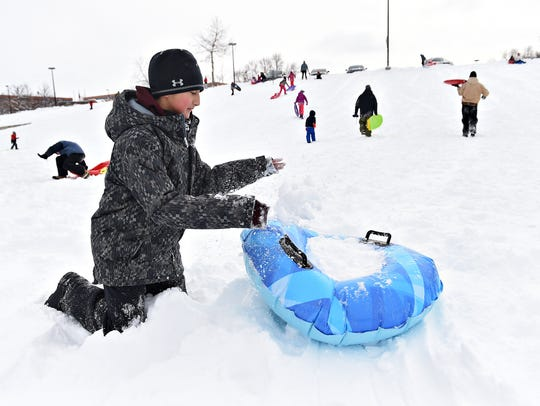 Shawn Hunger gathers snow to build a ramp at Edora