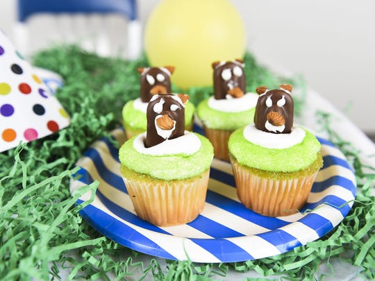 Candy bar groundhogs emerge from cupcakes in honor of Groundhog Day.