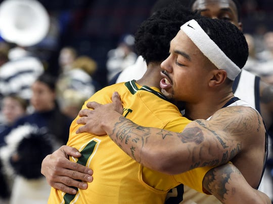 Monmouth's Justin Robinson, right, embraces Siena's Marquis Wright after Siena wins 89-85 in their MAAC Tournament semifinal basketball game on Sunday, March 5, 2017, at Times Union Center in Albany, N.Y. (Cindy Schultz / Correspondent)