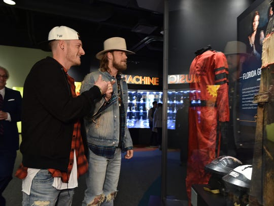 NASHVILLE, TN - MARCH 14:  Singer-songwriters Tyler Hubbard (L) and Brian Kelley (R) of Florida Georgia Line admire their display at The Country Music Hall of Fame and Museum debuts new American Currents Exhibition on March 14, 2017 in Nashville, Tennessee.  (Photo by John Shearer/Getty Images for Country Music Hall of Fame)