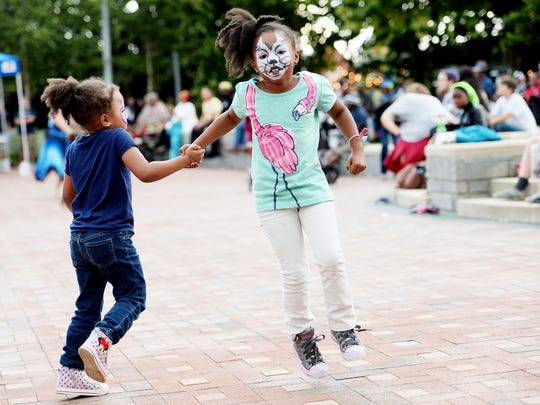 Sisters Scarlet, 5, left, and Paige Calloway, 7, dance at Goombay in Pack Square Park September 9, 2017.