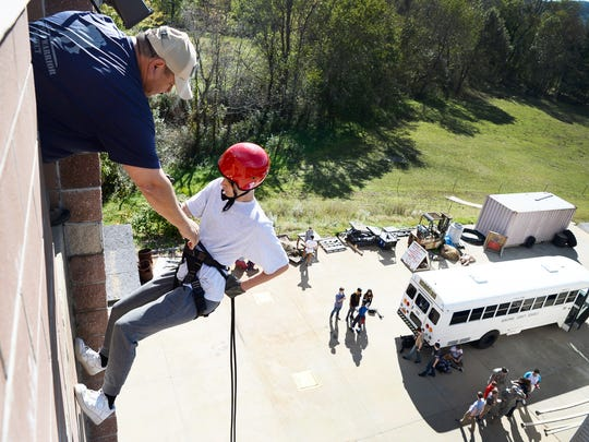 Chief Tony Gutierrez gives tips to Dakota Millwood, of Roberson High School, as he prepares to rappel down a training tower at the Swannanoa Fire Department October 18, 2017.