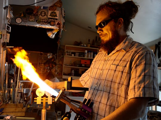 Jamie Wickliffe uses a torch to heat glass in his home studio in Fairview November 2, 2017.