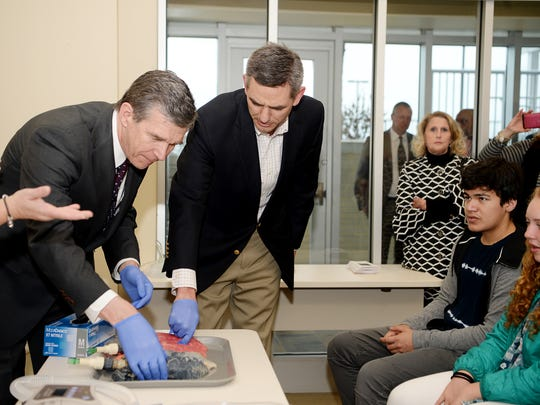 Gov. Roy Cooper, left, and Rep. Brian Turner, D-Buncombe, check out pig lungs as they learn about respiratory health with Valley Springs Middle School students for the Students@Work program March 27, 2018.