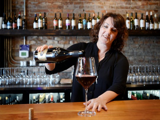 The District Wine Bar owner Lauri Nichols pours a glass of Verso Rosso negramaro primitivo in the River Arts District March 29, 2018.