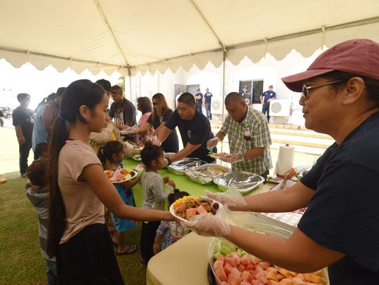 Guam Fire Department personnel served food for people