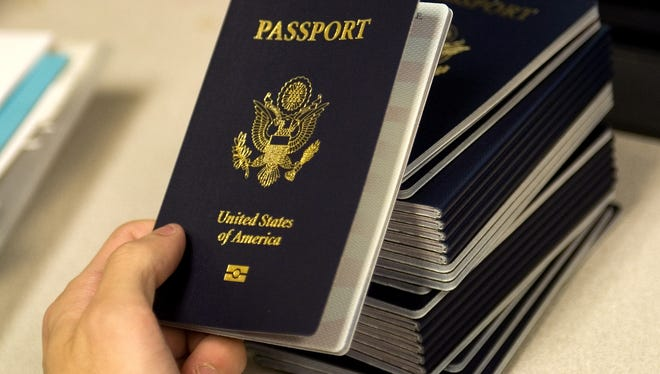 A US government official with the State Department's Passport Services reaches for a new blank US Passport with an embedded electronic chip to begin the process of entering personal data and the photograph of an applicant.