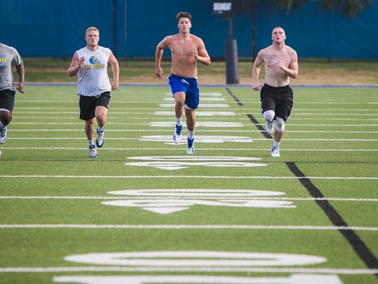University of Delaware football players do running, stretching and other exercise drills as part of their summer conditioning.
