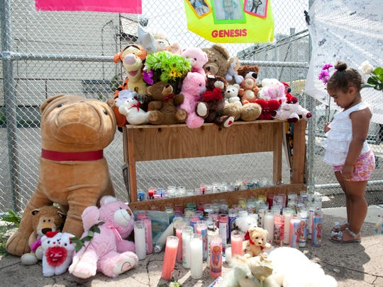 A child eyes a makeshift shrine at the spot where Genesis