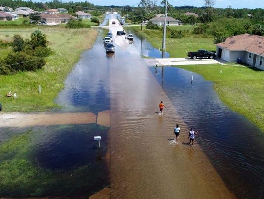 Children walk through flooded streets Tuesday, Sept.