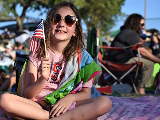 Paige Davis, 9, waves a miniature U.S. flag on July 3, 2018, during the July 3rd Pops Concert.