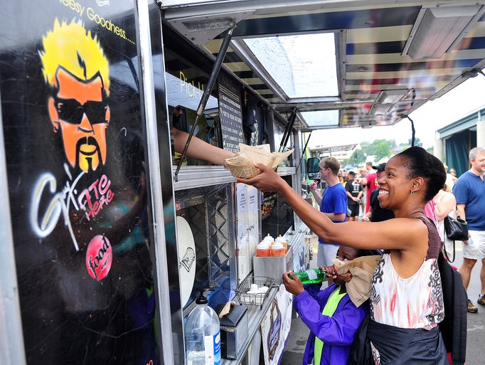 Erica Terrell, right, gets her food as she walks around with her daughter Erin, 7, during Nashville Street Food Awards at the Nashville Farmers' Market in Nashville, Tenn., Saturday, Aug. 30, 2014. A portion of proceeds will benefit Musicians' Corner.