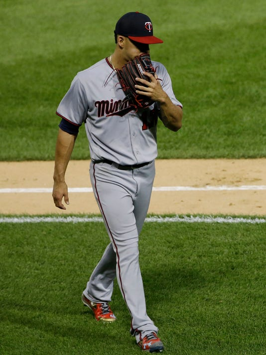 Minnesota Twins starting pitcher Jose Berrios covers his face with his glove as he walks back to the dugout after the second inning of a baseball game against the Chicago White Sox, Thursday, Aug. 24, 2017, in Chicago. (AP Photo/Nam Y. Huh)