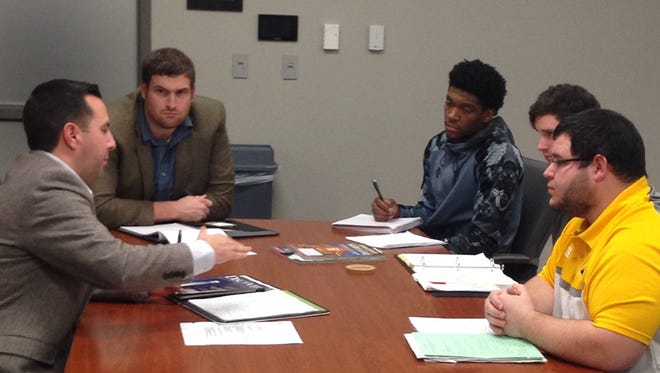 Biloxi Shuckers General Manager Chuck Arnold, left, and Chris Harris, director of media relations and broadcasting, meet with Southern Miss graduate students about a class project that involves marketing and promotions for the Minor League Baseball organization.