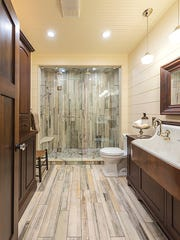 The distressed wood-look tile floor planks were used vertically in the shower to create the appearance of height.