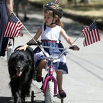 Meredith Heyen, 5, pets her dog Stitch during the Court-Chemeketa Fourth of July Kids Parade on Saturday, July 4, 2015.