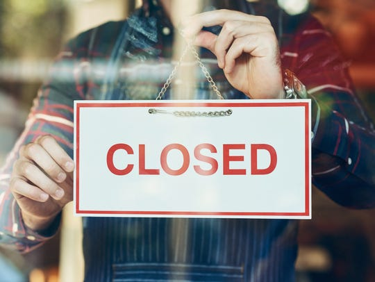 """A stock photo showing a woman putting a """"closed"""" sign"""