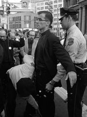Father James W. Harney is frisked by police in the park across from the Germania Building, 135 W. Wells St., after Harney and a group of anti-war protesters took draft records from the Selective Service Administration office and burned them in the park on Sept. 24, 1968. Harney and 13 others were arrested in the incident, and became known as the Milwaukee 14. This photo was published in the Sept. 25, 1968, Milwaukee Journal.