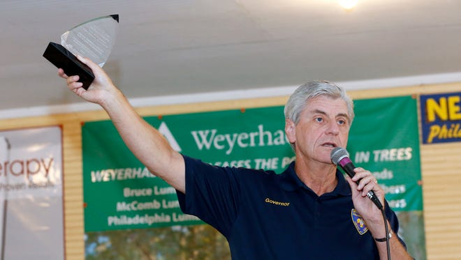Gov. Phil Bryant waves an education innovation award given to the state by a national organization during his address at Founder's Square at the 2016 Neshoba County Fair near Philadelphia.