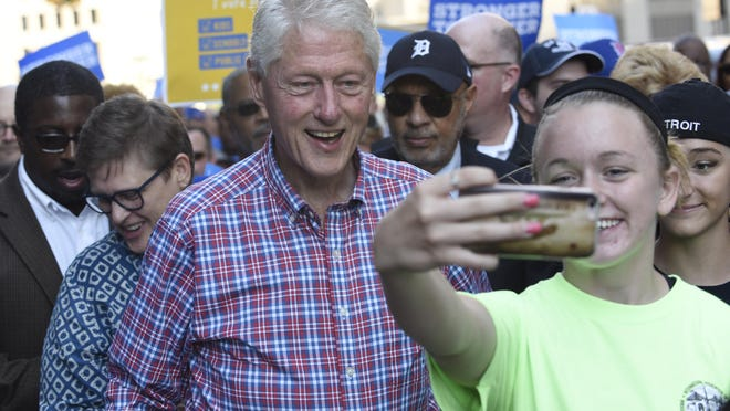 Former President Bill Clinton takes a photo with a young lady during the Labor Day parade.