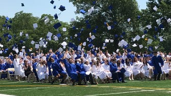 Millburn High School seniors toss their motarboards into the air at the conclusion of graduation exercises June 22.