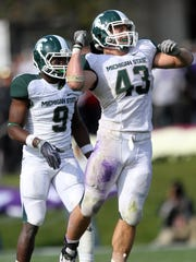 Michigan State linebacker Eric Gordon (43) celebrates stopping a drive by Northwestern during the fourth quarter of an NCAA football game at Ryan Field in Evanston, Illinois, on Saturday, October 23, 2010. The Michigan State Spartans defeated the Northwestern Wildcats, 35-27.