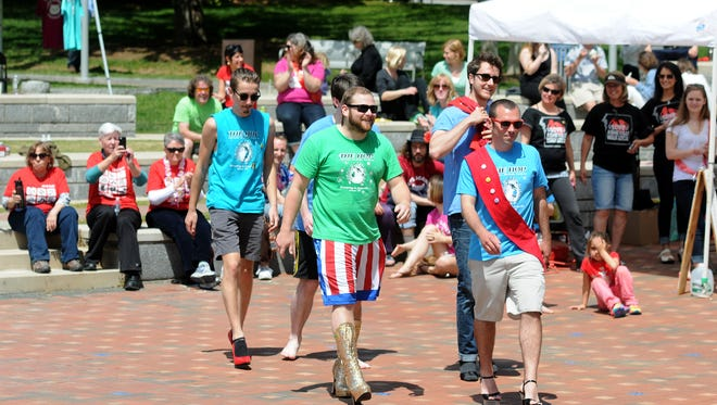 The team from The Hop approaches the stage to receive their award for fastest team during Walk a Mile Asheville at Pack Square Park on Saturday, May 2, 2015.