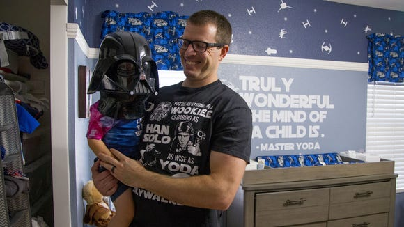 Huge Star Wars fan Andrew Stewart holds his son, Elliott,
