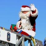 Santa waves to the crowd during last year's Pensacola Beach Surfin' Santa Parade.