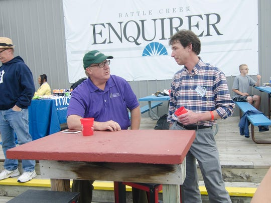 Jim Wright talks with Battle Creek Enquirer Executive Editor Mac McCullough during a 2015 Battle Creek Bombers game at C.O. Brown Stadium.