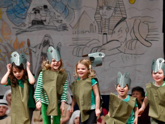 Hats go flying as frogs of the plague hop around during the children's Passover play at the Temple preschool.