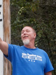 Paul Black waves to passing motorists next to displays he put up at the front of his property on Farm Road 141 across from the polling place at Glidewell Baptist Church.