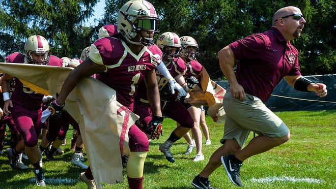 Eureka  College football coach Kurt Barth leads the team onto the field in this 2018 file photo.
