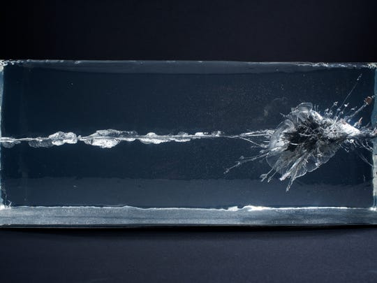 """The Propeller Group's """"AK-47 vs. M16"""" captures bullets colliding in ballistic gel. On display at the Phoenix Art Museum."""