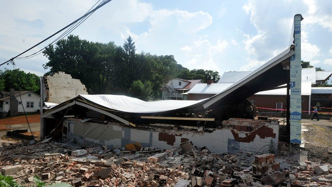 Officials investigate a building that collapsed on the corner of Haywood Road and Wellington Street in West Asheville on Wednesday.