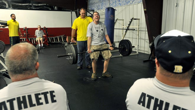 Alex Pott is spotted by volunteer John Hollifield as he does a deadlift during practice of the Buncombe County Special Olympics weight lifting team at WNC Barbell on Thursday.