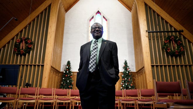 Pastor Charles Bates, of Fishersville United Methodist Church, stands for a portrait inside the sanctuary on Tuesday, Dec. 1, 2015. Bates was born in Liberia and fled the country after a civil war broke out, ultimately making his way to the United States.