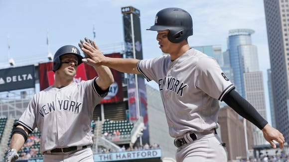 New York Yankees' Brett Gardner, left, congratulates Rob Refsnyder after he scored on Gardner's sacrifice fly off Minnesota Twins pitcher Ryan Pressly in the ninth inning of a baseball game Saturday, June 18, 2016, in Minneapolis.