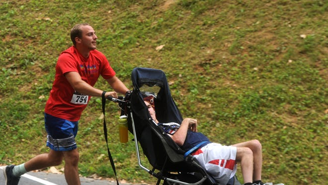 Dustin Thurston, right, has cerebral palsy, but it hasn't stopped the 21-year-old Weyers Cave man from participating in several athletic events, including Tuesday's Firecracker 5K in Staunton. Thurston's friend, Isaac Diehl, pushed the wheelchair during part of the race.
