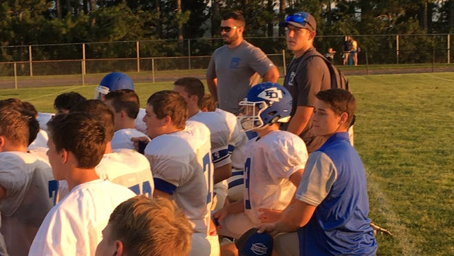 Sam Hill, in his blue coaching shirt, kneels behind his Fort Defiance teammates after a scrimmage at Riverheads Saturday, Aug. 19. Hill, a junior, will miss the season with possible autoimmune hepatitis.