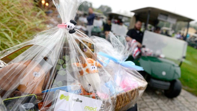 """Golfers drive past some of the baskets to be auctioned off at the """"Fly High 22"""" memorial golf tournament in honor of Amanda Strous. Strous, a Dallastown graduate, was murdered in June of 2016 in her North Carolina apartment."""