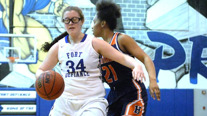 Fort Defiance's Kaleigh May (34) is guarded by Heritage's Tatiyana Graham (21) Monday during a Region 3C quarterfinal basketball game. Heritage won 47-40.