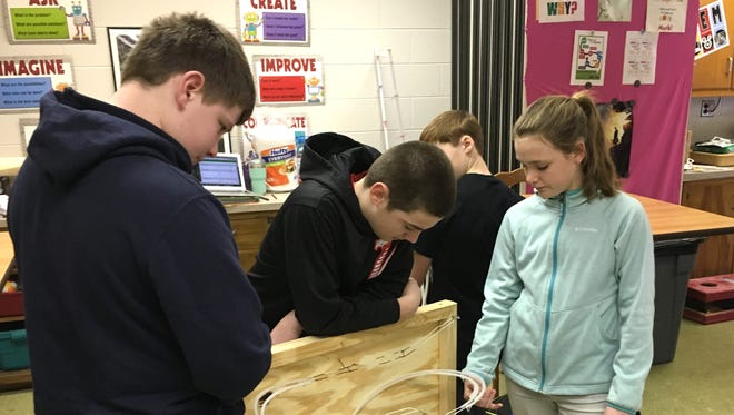 Henry Gutshall, from left, Caden Richter and Adriana Shields work on figuring out the next step of their gravity roller coaster track, a project the three seventh-graders did in Stewart Middle School's STEM class.