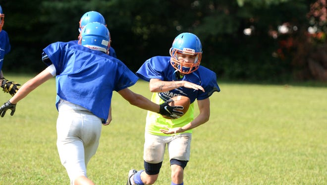 Kshawn McCarthy takes a handoff during Grace Christian football practice Wednesday, Aug. 22.